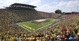 Autzen stadium filled with people and band on field with large flag